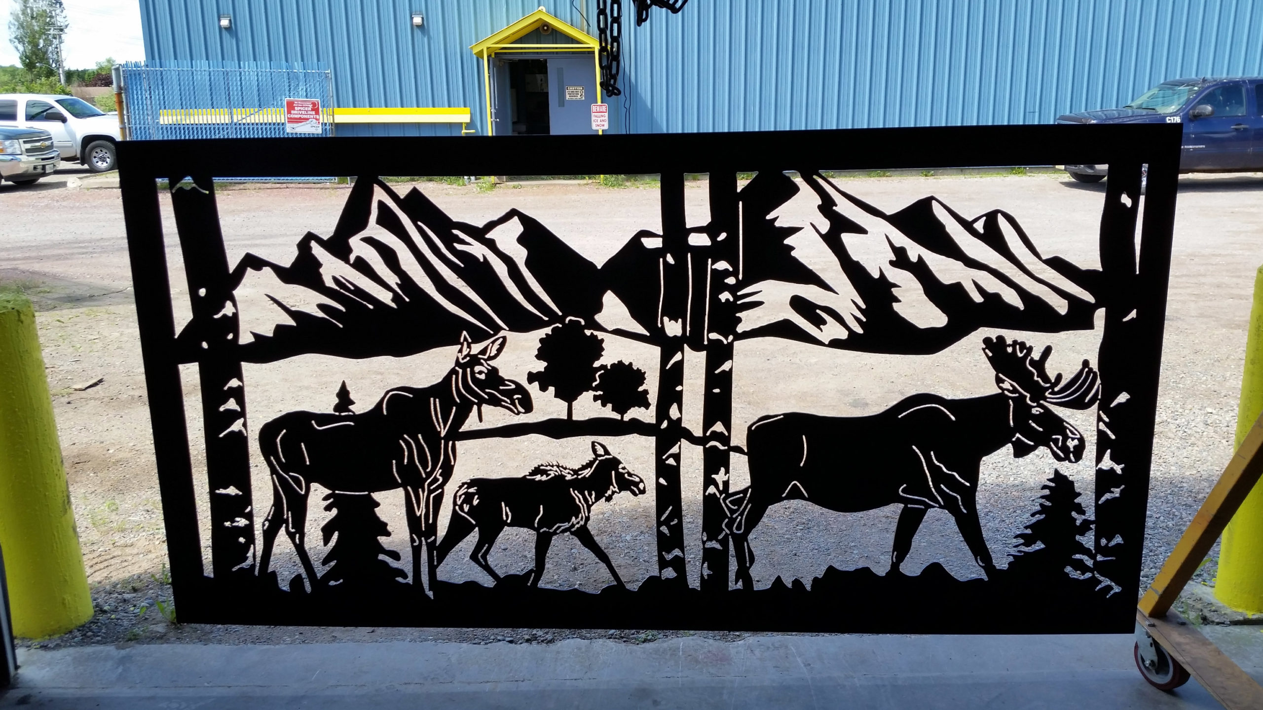 Metal artwork design of a moose family as part of a steel gate structure